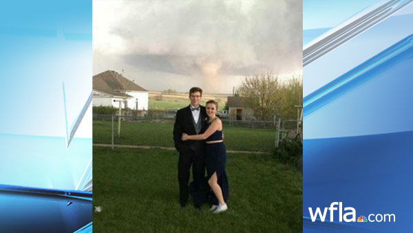 In this Saturday, May 7, 2016, photograph provided courtesy of Heidi Marintzer and taken with a mobile phone, Charlie Bator, left, and Ali Jolie Marintzer pose for a photograph before going to prom at the local high school as a tornado skips...