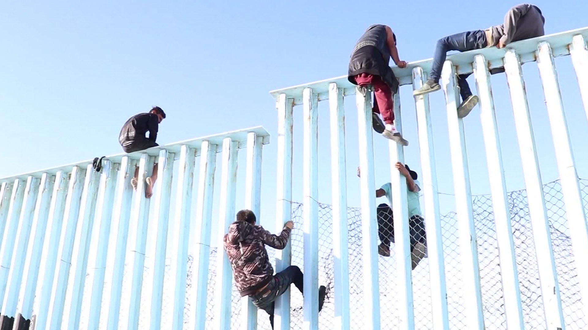 Video shows migrants climbing US-Mexico border fence