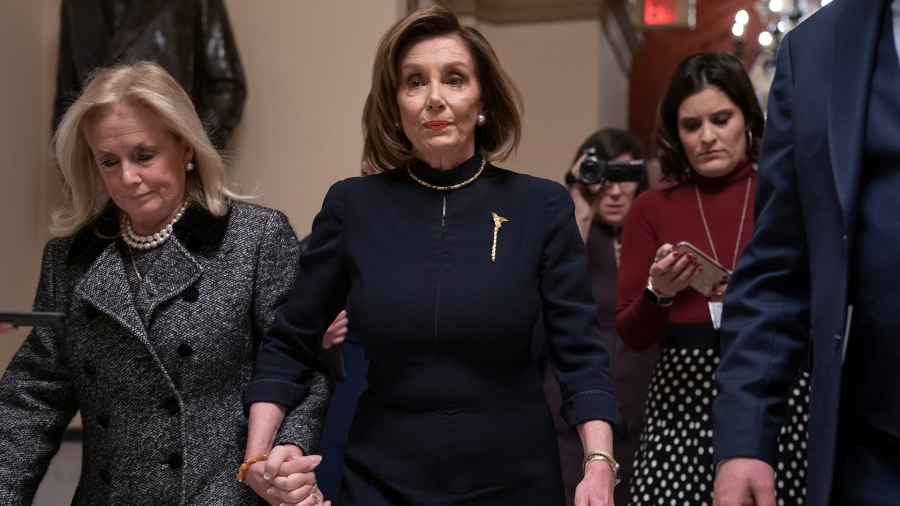 Speaker of the House Nancy Pelosi, D-Calif., holds hands with Rep. Debbie Dingell, D-Mich., as they walk to the chamber where the Democratic-controlled House of Representatives begins a day of debate on the impeachments charges against President Donald Trump for abuse of power and obstruction of Congress, at the Capitol in Washington, Wednesday, Dec. 18, 2019. (AP Photo/J. Scott Applewhite)